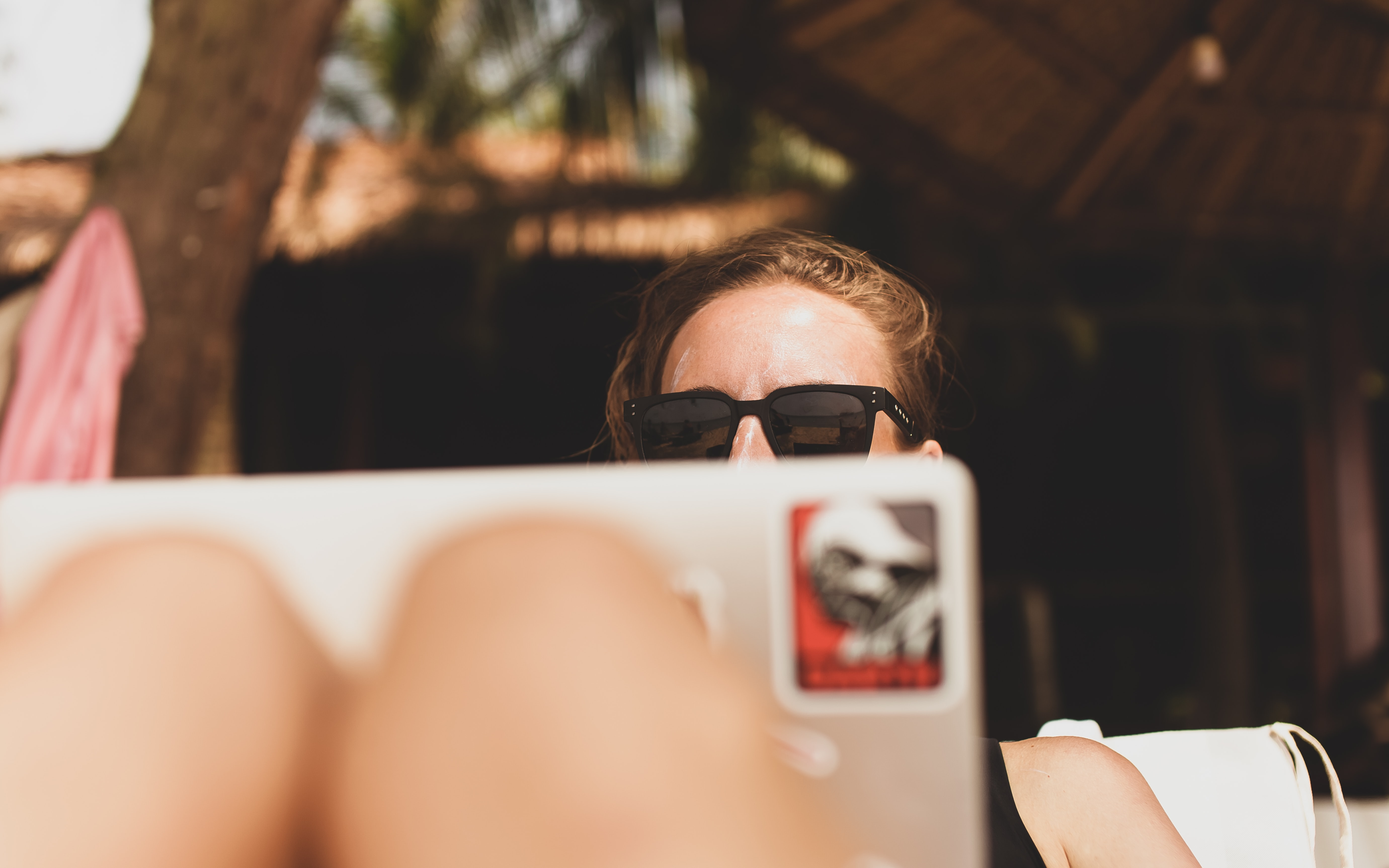 Young professional on her laptop while sunbathing